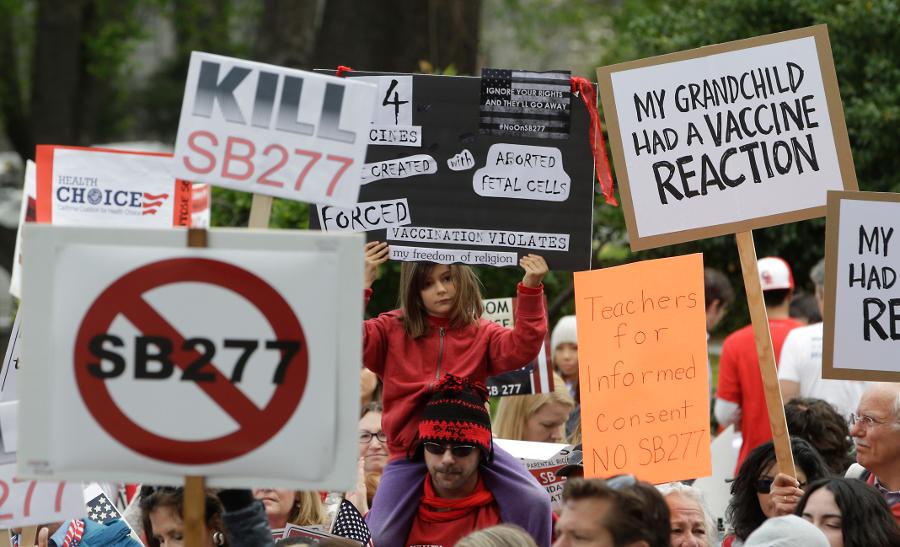 Протестующие против мер, направленных на вакцинацию школьников в Калифорнии, на митинге у здания Капитолия в Сакраменто.