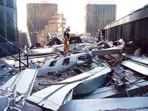 Обломки на крыше пятого здания ВТЦ, включая кусок фюзеляжа, на котором чётко видны пассажирские иллюминаторы.
